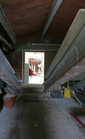 dusty attic of a big house and the door to go in the laundry room with the clothes hanging