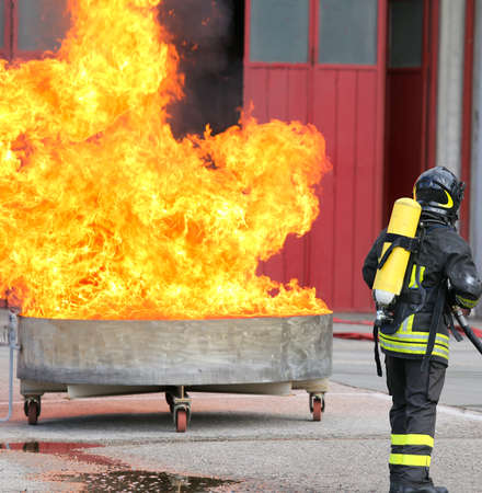 Firefighters exercise with a tank full of flames and very hot fire and the fireman with oxygen tanks