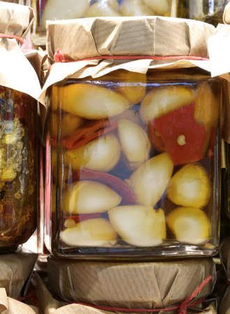 glass jar with garlic cloves with red peppers in oil on sale in the stall of the Mediterranean country