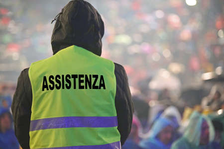 italian guard with the phosphorescent vest at the outdoor concert and during a storm and the text ASSISTENZA that means Assistance in Italian Language