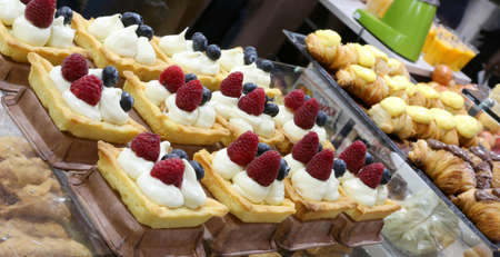 many pastries of pastry with raspberries and blueberries and a lot of whipped cream