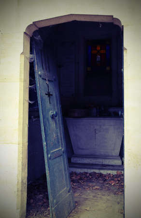 terrifying broken door of an abandoned grave in an old cemetery with vintage effect
