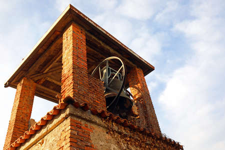 ancient medieval brick bell tower with bronze bell and blue sky with some clouds Zdjęcie Seryjne