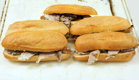 five sandwiches stuffed with roast pork for sale in the food stand on the street Stock Photo