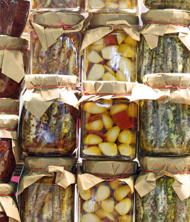 many jars with garlic cloves with peppers and marinated anchovies prepared by hand in a Mediterranean country