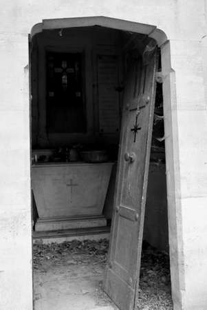 broke door of an old grave in the abandoned cemetery with black and white toned effect