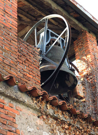 ancient brick bell tower with the historic large bronze bell Stock Photo
