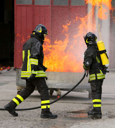 two intrepid firefighters during the exercise with a tank full of flames and very hot fire and the fireman with oxygen tanks Stock Photo