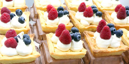 many pastries stuffed with cream and berries for sale in a pastry shop 写真素材