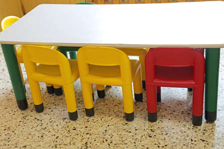 inside a school classroom of a kindergarten with small plastic chairs without children