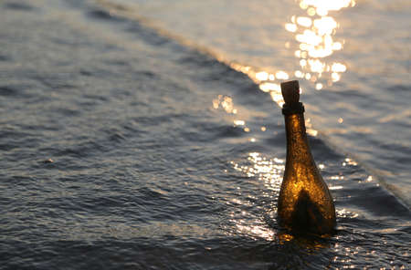 bottle with the secret message in the sea at sunset in the summer