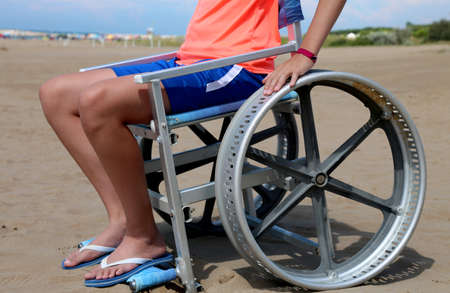 disabled boy on a special wheelchair at a beach