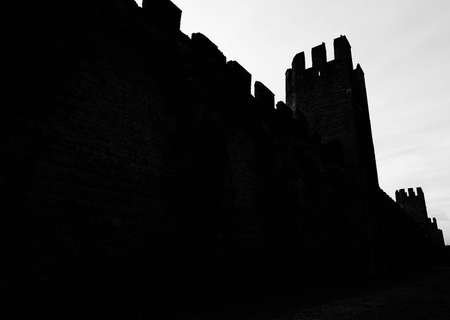 dark black silhouettes of the ancient medieval walls that protected the city