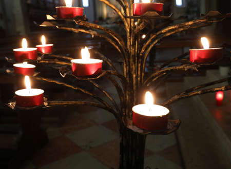 candlestick with lit candles inside a church as a sign of faith and devotion