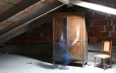 gloomy attic with an old wooden wardrobe and the movement of a ghost