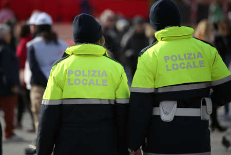 two italian police officers with uniform with the text POLIZIA LOCALE which means City Local Police in Italian language during a check on the street Banco de Imagens