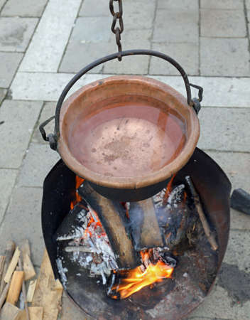 old cauldron of copper with boiling water and a wood fire below Banco de Imagens