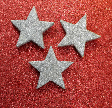 three silver stars on bright red glittery background illuminated