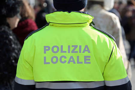 Italian Policeman with uniform and the text POLIZIA LOCALE that means Local Police in the square with many people Stock fotó