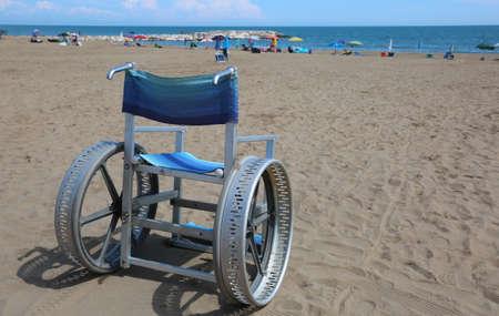 Silla de ruedas especial en aluminio y grandes ruedas para moverse sobre la arena de la playa Foto de archivo