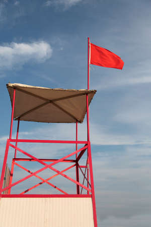 Turret of Lifeguard and big red flag in summer