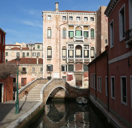 ancient palace in Venice with the stepped bridge and the navigable canal without people