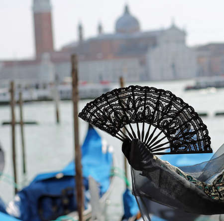 fan in the hand of the woman in Venice in Italy and the Church of Saint George in Background