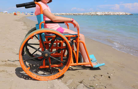 Little girl on the wheelchair on the beach at resort in summer