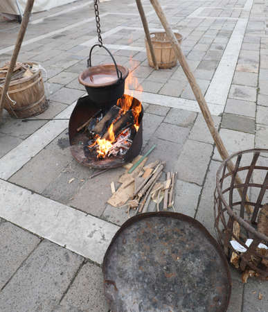 Outdoor camp during a historical re-enactment with bonfires and an old copper cauldron full of boiling water