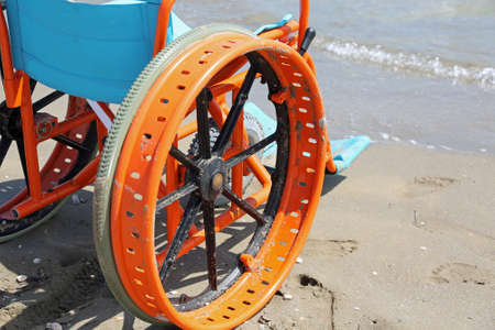 detail of the particular wheelchair with the wheels modified to move on the sandy beach by the sea Reklamní fotografie