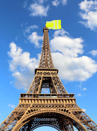 Big jacket such as a flag symbol of Yellow vests movement on Eiffel Tower in Paris France seen from below