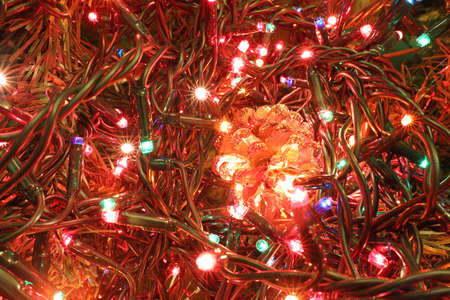 many shimmering lights to decorate and a golden pinecone on the tree Standard-Bild