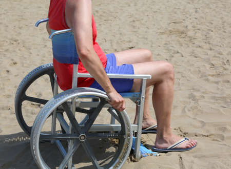 young man on wheelchair with wheels modified to move even on sandy beach