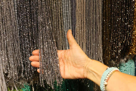 hand of woman who chooses the necklaces in the costume jewelry shop