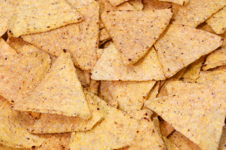 background of many salted yellow tortilla chips made with corn vegetables oils salt in triangle shapes