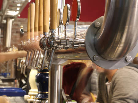 taps of a pub specializing in beers and the big steel tube Stok Fotoğraf