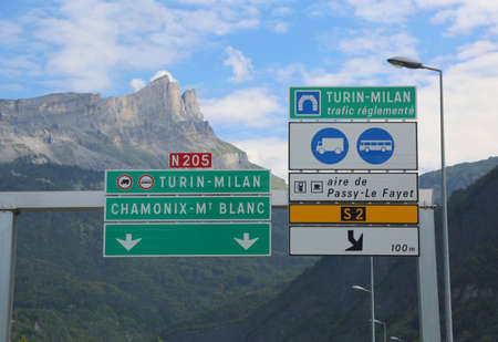 road sign on the border between Italy and France with directions to go to Turin Milan using the motorway tunnel