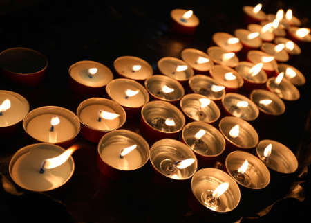 many lit candles in the gravestone of the cemetery without people