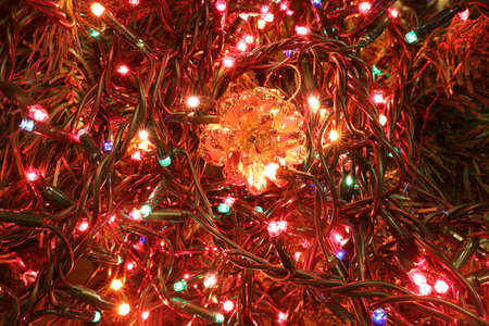 christmas background with golden pine cone and colored lights of christmas tree