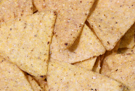 background of salted yellow tortilla chips made with corn vegetables oils salt in triangular shapes