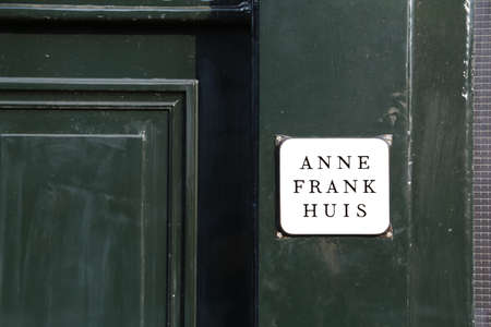 Amsterdam, Netherlands - August 22, 2017: entrance of the house of the Jewish young girl ANNE FRANK with the text on the green door that means Anne Frank House in Dutch Language 報道画像