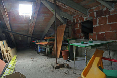 dusty attic attic with broken and old material and a skylight from which sunlight enters