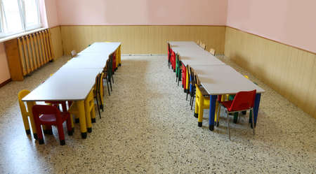 large nursery room used as a refectory with tables and small chairs without children