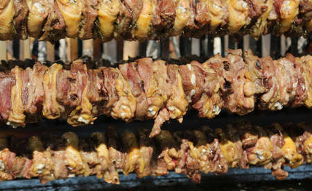 large spit with chicken meat and pork cooked slowly in the rotisserie of the village fair Stock Photo