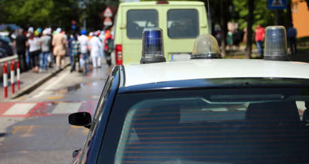 car of police with sirens during parade of protesters