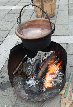 old copper cauldron over the fire made of burning woods and boiling water