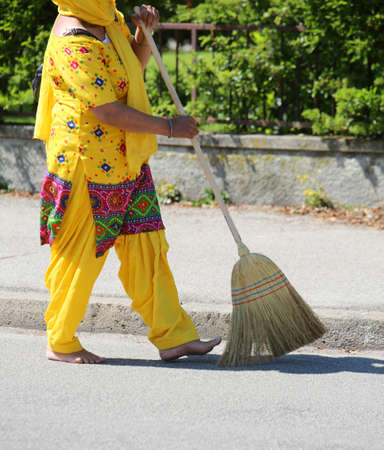 woman of sikh religion with broom in the street during parade Stock Photo
