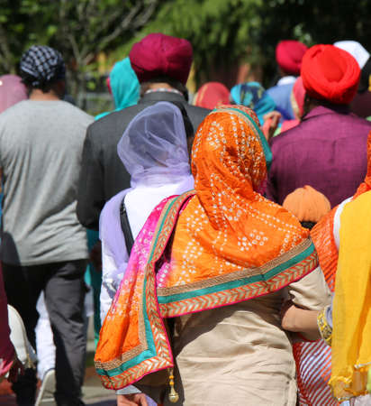 women and men during religious parade with viels and turbans