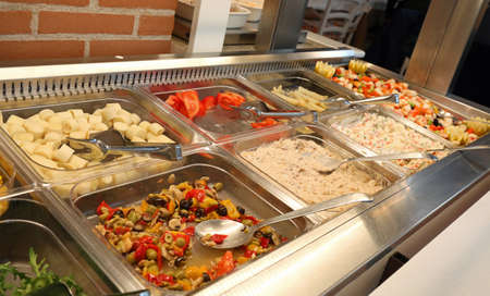 Inside a self service restaurant with many raw and cooked foods