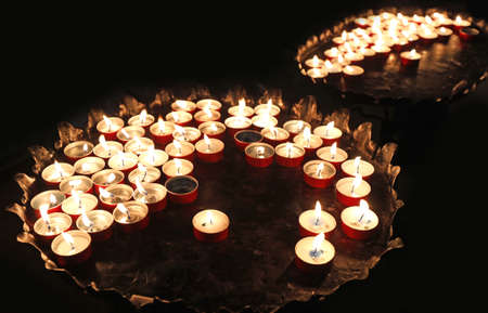 many candles in the place of worship during the religious ceremony Stock Photo